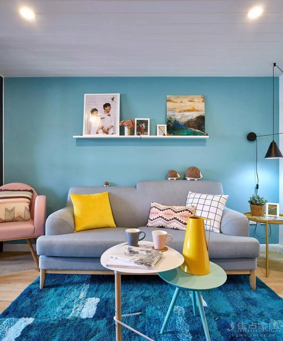 客厅沙发背景同样是孔雀蓝的墙面,地板上铺上一块深蓝色的地毯图片